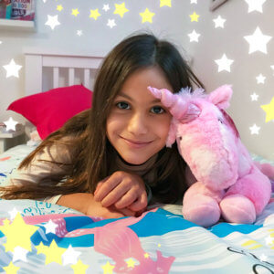 Girl on bed with GirlZone fluffy Unicorn